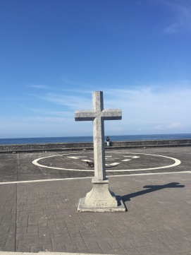 Beyond the cross is a cliff overlooking the ocean